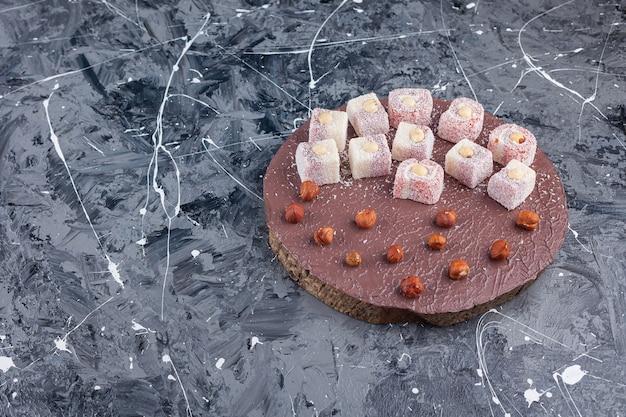 Türkisches lokum mit haselnüssen auf einem holzstück.