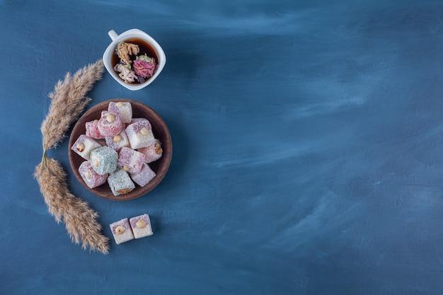 Türkisches lokum mit haselnüssen und einer tasse kräutertee.