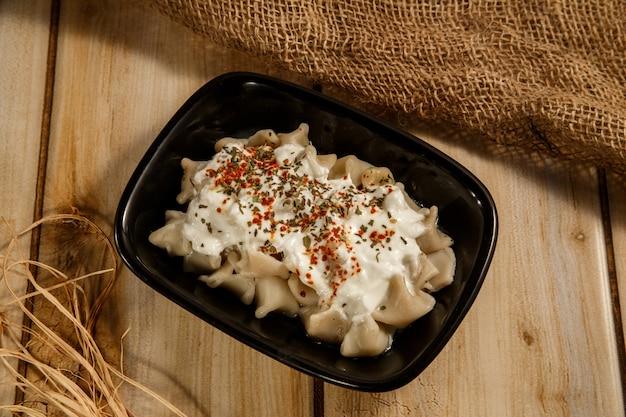 Türkisches manti manlama auf platte mit rotem pfeffer, tomatensauce, joghurt und minze