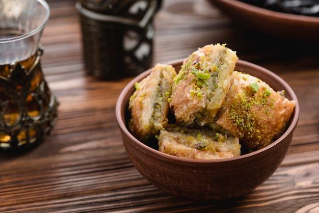Türkisches nachtischbaklava mit pistazie in der tönernen schüssel auf hölzernem schreibtisch