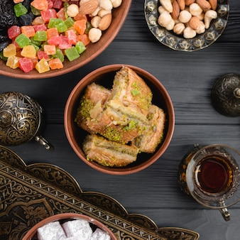 Türkisches nachtischbaklava mit trockenfrüchten und nüssen auf hölzernem schreibtisch