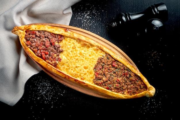Türkisches pide-gericht mit drei verschiedenen füllungen: lamm-, rind- und cheddar-käse auf einem schwarzen tisch. nahaufnahme, selektiver fokus