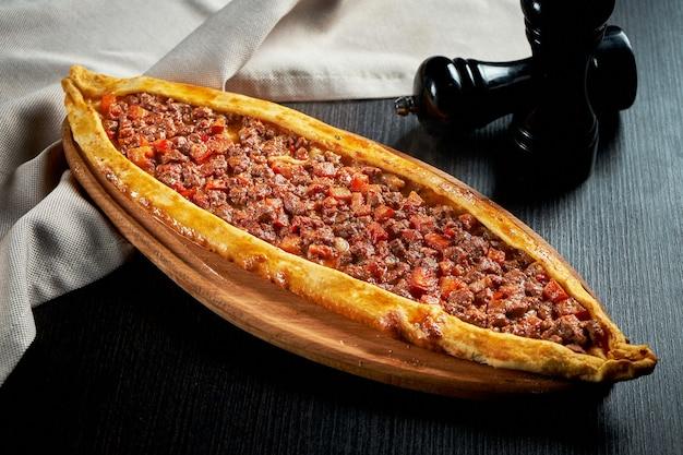 Türkisches pide gericht mit rindfleischscheiben, tomaten auf schwarzem tisch