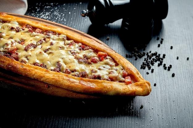 Türkisches pide-gericht mit rindfleischscheiben, tomaten und cheddar-käse auf schwarzem tisch