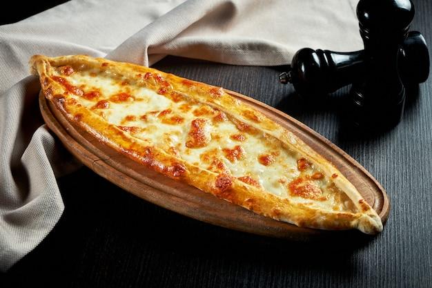 Türkisches pide gericht mit tomaten und gesalzenem käse auf schwarzem tisch