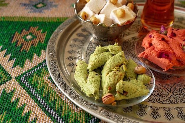 Türkisches süßes baklava auf metalltablett mit türkischem tee