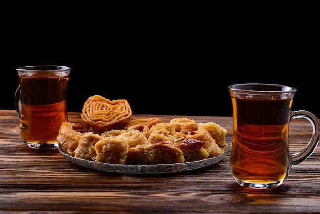Türkisches süßes baklava auf teller mit türkischem tee.
