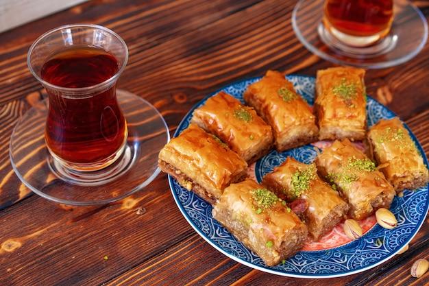 Türkisches süßes baklava mit türkischem tee auf hölzernem hintergrund