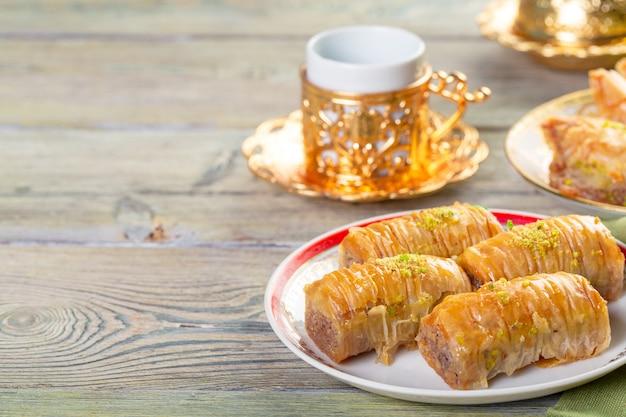 Türkisches traditionelles nachtisch-baklava mit tee auf dunkelheit. frisches und gesundes dessert.
