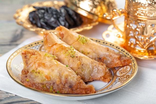 Türkisches traditionelles nachtisch-baklava mit tee auf dunkelheit