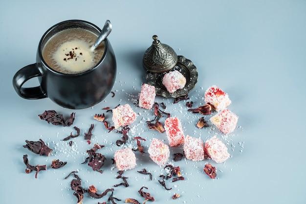 Türkisches vergnügen lokum in einer metallischen untertasse mit einer tasse kaffee