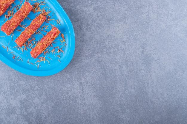 Türkisches vergnügen rahat lokum mit pistazien auf blauem holzbrett