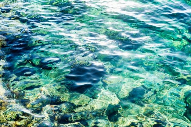 Türkise oberfläche des meerwassers mit sonnenblendung. hintergrund.