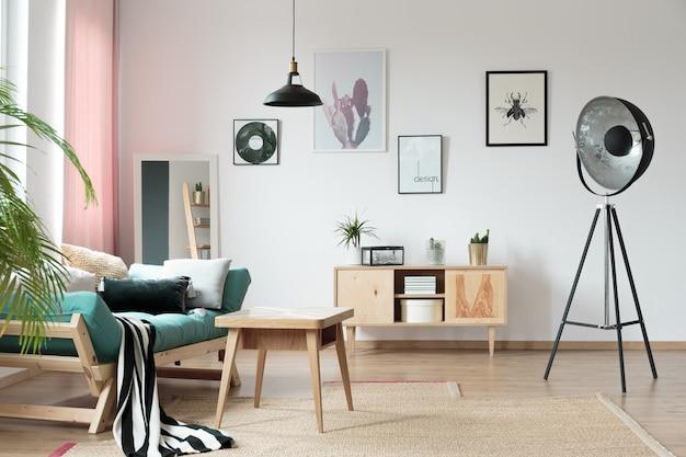 Türkisfarbene couch mit kissen im warmen wohnzimmer mit designerlampe und holztisch auf teppich