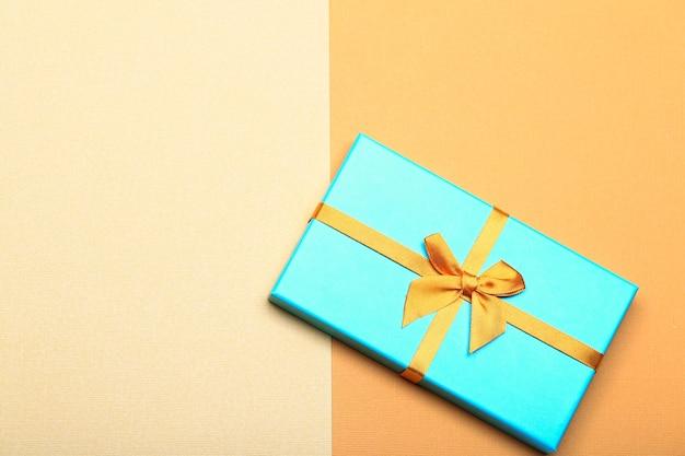Türkisfarbene geschenkbox auf gelbem papierhintergrund