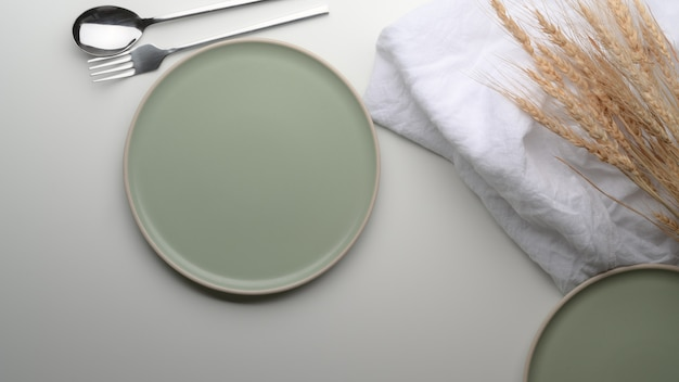 Türkisfarbene keramikplatten, besteck, serviette und goldener weizen auf weißem esstisch