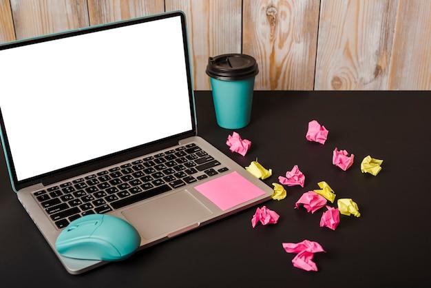 Türkisfarbene maus; haftnotiz; tasse zum mitnehmen; zerknittertes papier und laptop zeigen weiße bildschirmanzeige auf schwarzem hintergrund