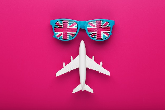 Türkisfarbene sonnenbrille mit flagge großbritanniens in gläsern auf verrückter rosa oberfläche mit weißem flugzeug