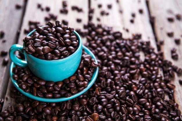 Türkisfarbene tasse mit kaffeebohnen auf einem holztisch.