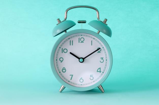 Türkisfarbener klassischer wecker um zehn uhr morgens auf tadellosem hintergrund. start des arbeitstageskonzeptes