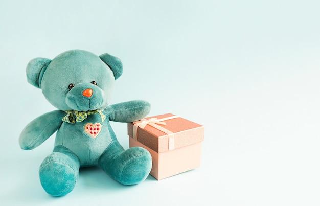 Türkisfarbener weicher teddybär mit gesticktem herzen hält eine geschenkbox und eine schleife