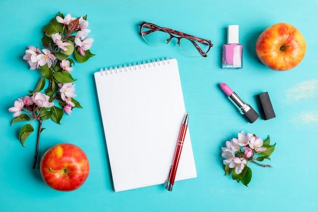 Türkisfarbenes layout mit weißem notizblock mit stift, brille, lippenstift und nagellack, äpfeln und apfelbaumzweigen.