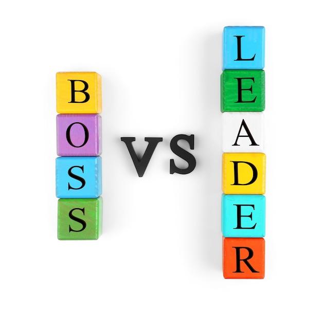 Türme aus bunten holzwürfeln und schwarzen buchstaben, die text boss vs leader einzeln auf weiß bilden