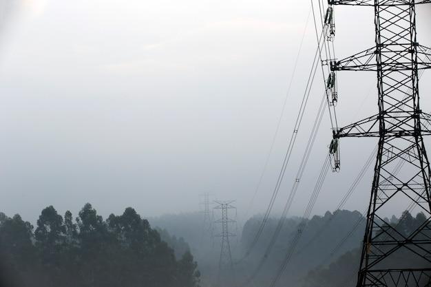 Türme der elektrischen kraftübertragung im nebel