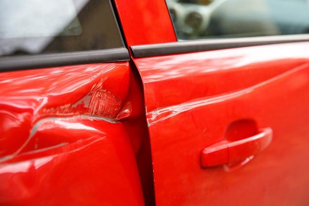 Türrotes auto bei einem tiefen dellenunfall beschädigt, kratzer an den türen