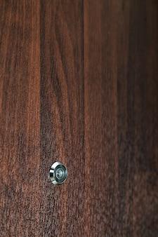 Türspion auf massivholz-textur-hintergrund. vom eingang zum zimmer. sicherheitsvideoüberwachungskonzepte sind ein solider brauner struktureller raum. platz für text, bildunterschrift oder logo