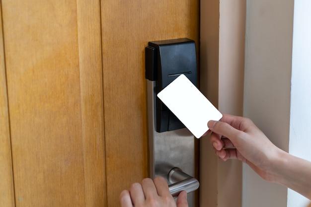 Türzugangskontrolle - frauenhand, die weiße modellschlüsselkarte hält, um tür zu verriegeln und zu entriegeln. digitales türschloss.