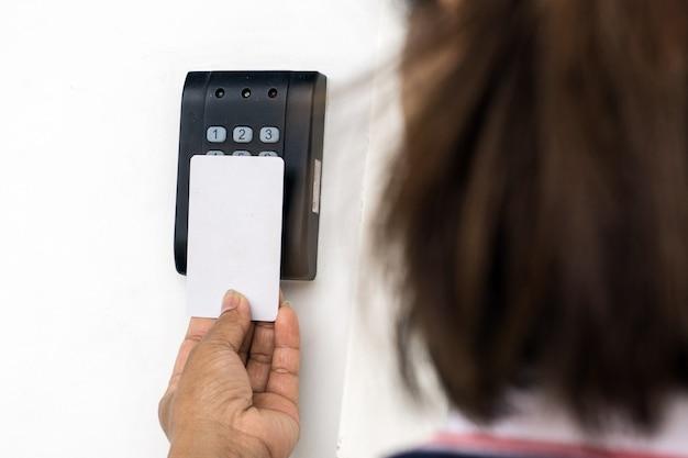 Türzugriffssteuerung - junge frau, die eine schlüsselkarte hält, um tür zu sperren und freizugeben.