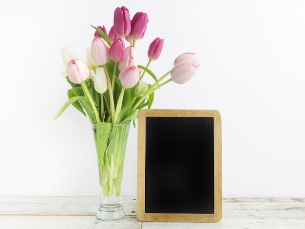 Tulpe mit leerem bilderrahmen auf weißem holztisch