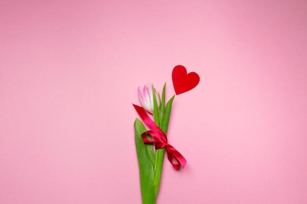 Tulpe und kleines rotes herz auf rosa hintergrund