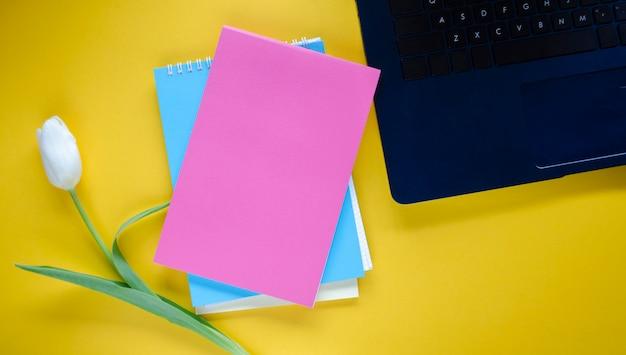 Tulpe und notizbücher neben einem laptop
