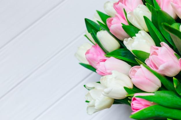 Tulpen auf hölzernem hintergrund. blumenstrauß. blumenstrauß für die liebe. weihnachtskarte mit kopierplatz.