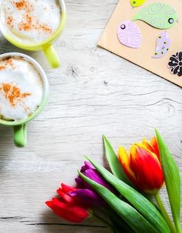 Tulpen auf holz mit zwei tassen kaffee. einladungspostkarte zum muttertag oder zum internationalen frauentag. frühlingsblumen, bunte vögel. handgemachtes origami. kräftige pastelle. cappuccino mit zimt.