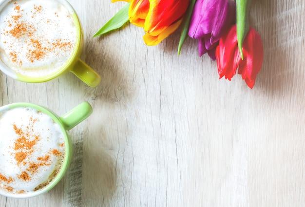 Tulpen auf holzhintergrund mit zwei tassen kaffee. einladungspostkarte zum muttertag oder zum internationalen frauentag. kräftige pastelle. cappuccino mit schaumzimt und blumen.