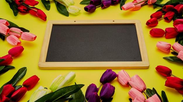 Tulpen auf holztisch mit schwarzem leerem kreidebrett
