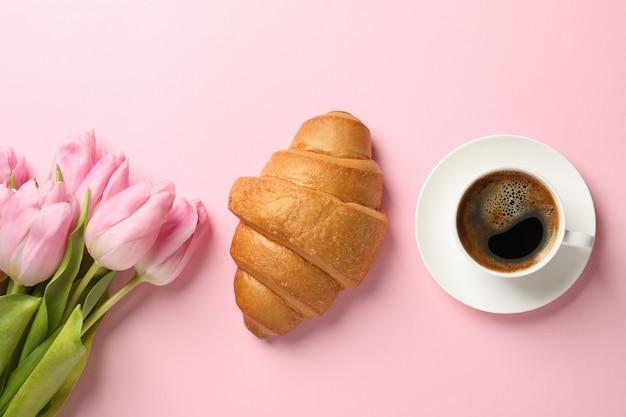Tulpen, croissant und tasse kaffee auf rosa hintergrund, draufsicht