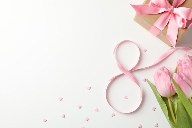 Tulpen, geschenkbox, acht aus band und kleinen herzen auf weißem hintergrund, platz für text