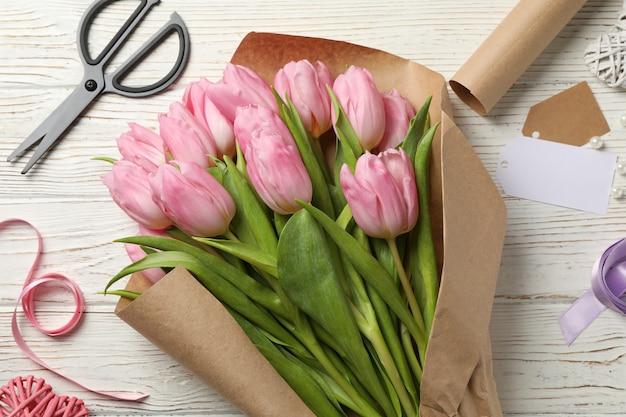Tulpen im bastelpapier auf hölzernem hintergrund, draufsicht