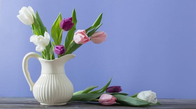 Tulpen im krug auf violetter oberfläche