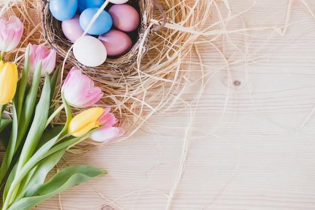 Tulpen in der nähe von eiern auf heu