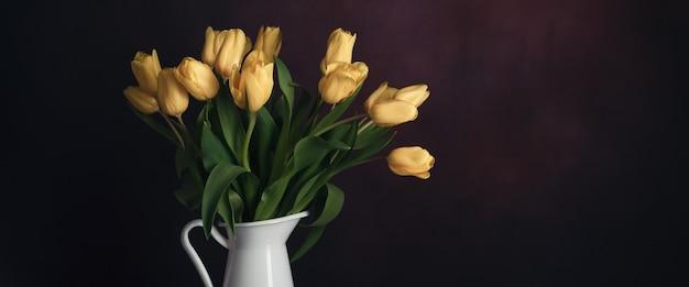 Tulpen in einem krug. klassisches stillleben mit einem strauß gelber tulpenblumen in einem weißen vintage-krug an einer dunklen wand und einem alten holztisch.