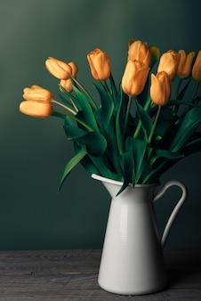 Tulpen in einem krug. klassisches stillleben mit einem strauß zarter tulpenblumen in einem weißen vintage-krug an einer grünen wand und einem alten holztisch.
