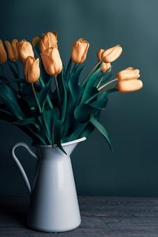 Tulpen in einem krug. klassisches stillleben mit einem strauß zarter tulpenblumen in einem weißen weinlesekrug auf grünem hintergrund und einem alten holztisch.