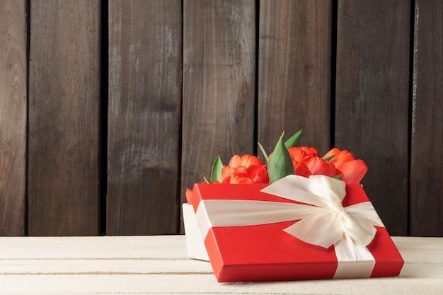 Tulpen in einer geschenkbox. strauß roter frühlingsblumen in einer roten schachtel.