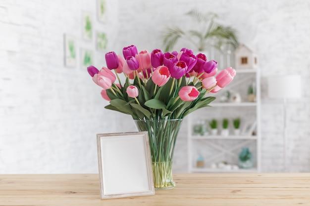 Tulpen in einer vase auf einem holztisch. skandinavisches interieur. attrappe, lehrmodell, simulation.