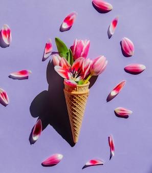 Tulpen in eistüte auf lila oberfläche. ansicht von oben